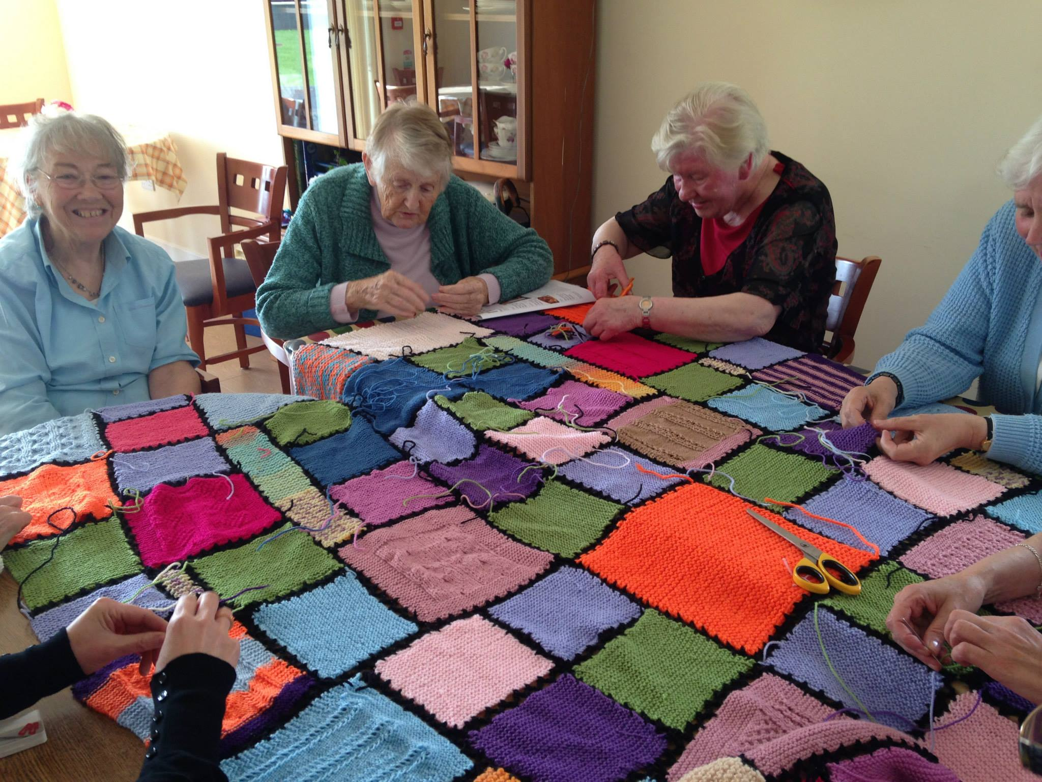 Some of the clients busy knitting a patchwork quilt to raffle at the Christmas raffle.
