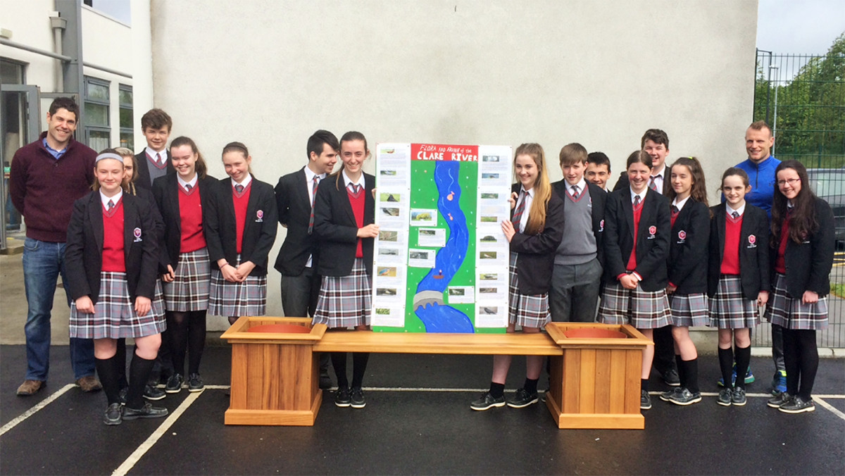 Our class with the bench, flower pots and poster, Teachers Mr Donnellan and Mr Kiely.